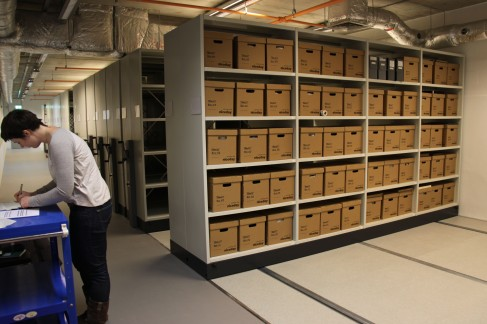 Photograph of Collections Assistant Eleanor Mills checking off items as they arrive in new archive facility. Rows of roller racking containing archival boxes can be seen in the background.